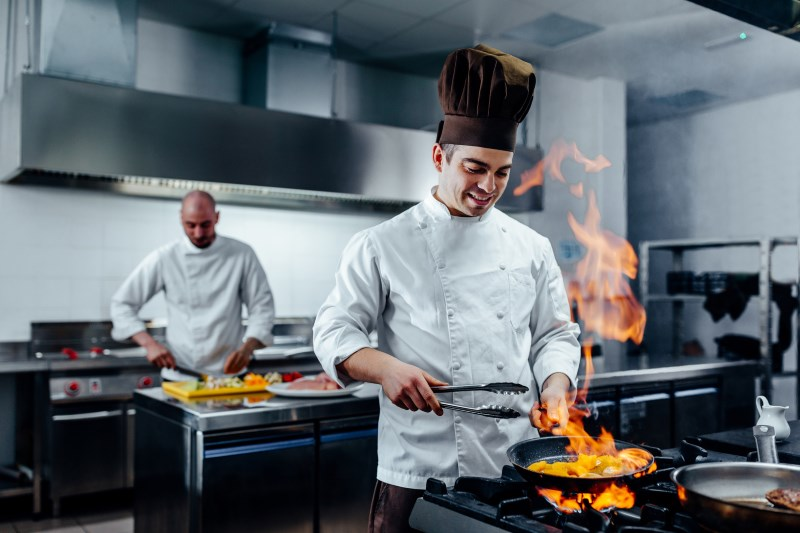 Cropped shot of a young male chef flambeing in a professional kitchen